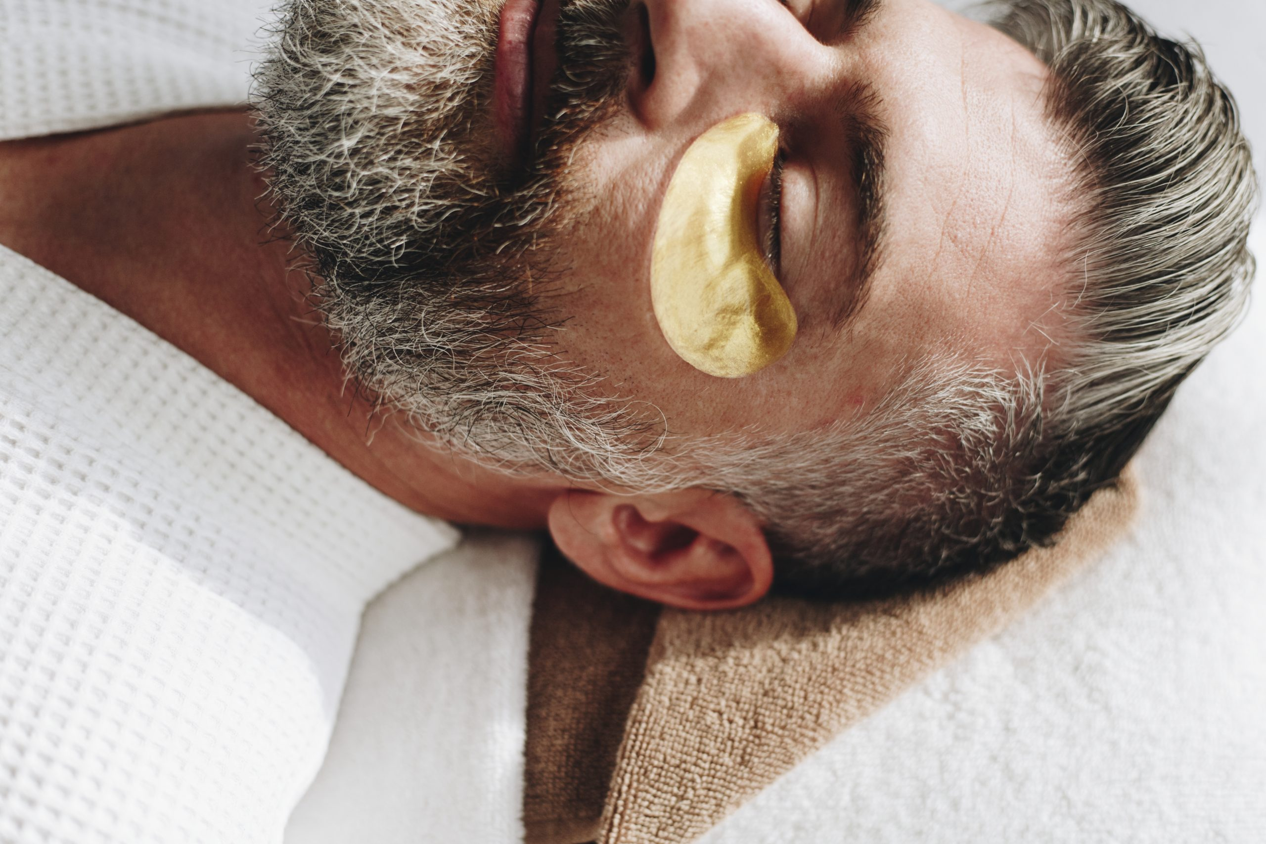 Man relaxing with a golden eye mask treatment